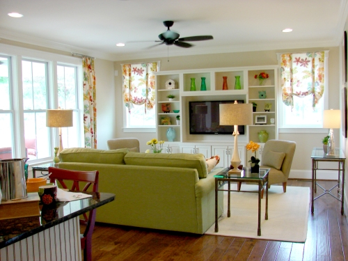 This neutral green living room has red and orange accents.